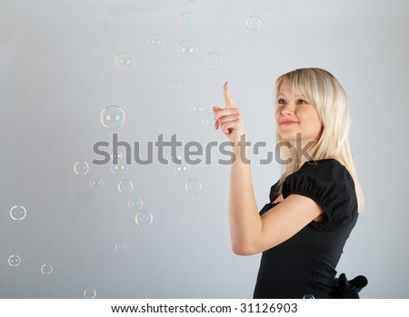 Young beautiful girl catch soap bubbles on gray background
