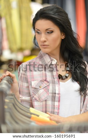 young beautiful girl chooses clothes in shop