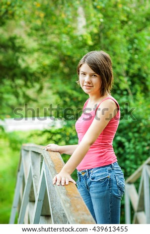 Young beautiful girl costs on bridge and keeps for its handrail.