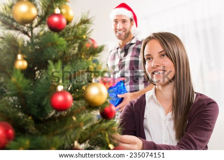 Young beautiful girl decorates the Christmas tree while her boyfriend holds a Christmas gift. - stock photo