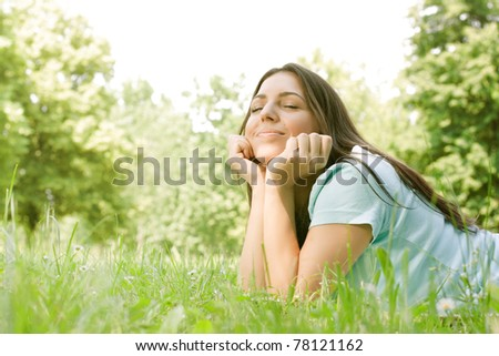 Young beautiful girl dreaming on green field.