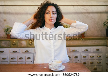 young beautiful girl drinking coffee in a cafe.attractive businesswoman with long curly hair drinking coffee in a coffee-shop and straightens hair - stock photo