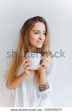 young beautiful girl drinking morning coffee from a large white Cup, posing in front of a white wall, smiling, morning outdoor portrait - stock photo