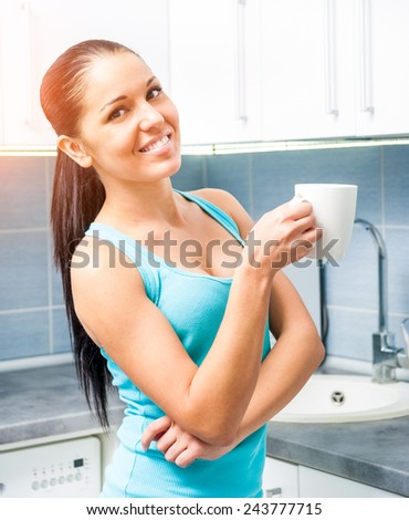 young beautiful girl drinking tea from a mug at home in the kitchen - stock photo
