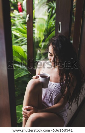 Young beautiful girl drinks morning tea on a windowsill at home in tropical garden