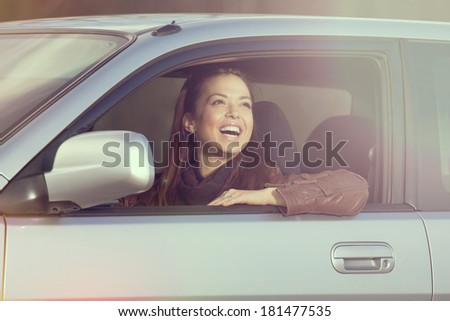 Young, beautiful girl driving a car and looking through a window - stock photo