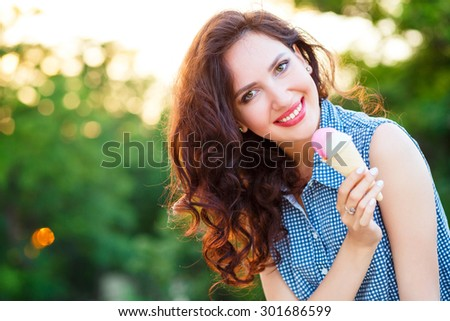 Young beautiful girl eating ice cream cone in the city park in the summer - stock photo