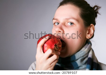 young beautiful girl eating pomegranate