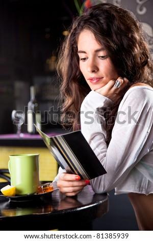 Young beautiful girl enjoying reading in cafe bar - stock photo