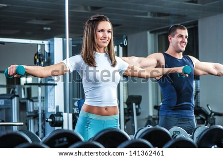Young  beautiful girl  exercise with  personal trainer - stock photo