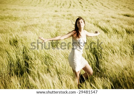 Young beautiful girl feeling freedom in a field. - stock photo