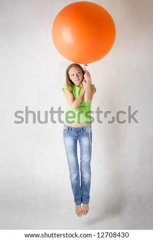 Young beautiful girl flying on balloon