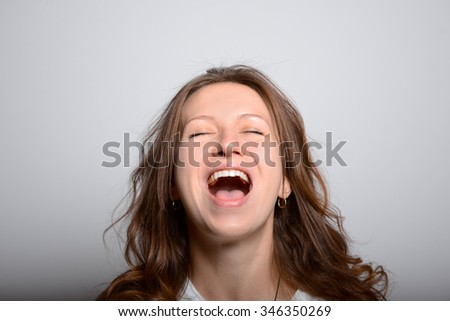 young beautiful girl happy and laughing, lifestyle concept isolated studio shot on a gray background
