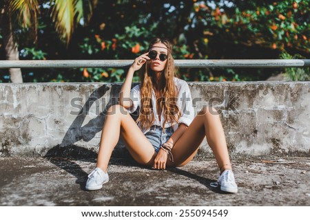 young beautiful girl hippies in sunglasses poses next to an abandoned house - stock photo