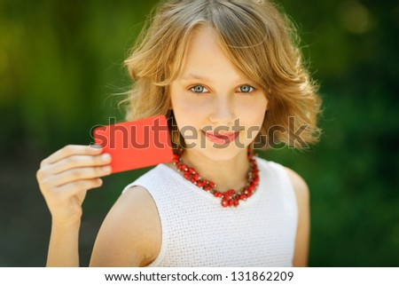 Young beautiful girl holding a blank credit card outdoor over green grass background - stock photo