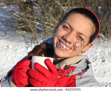 Young beautiful girl holding a cup of tea / coffee in winter park - stock photo