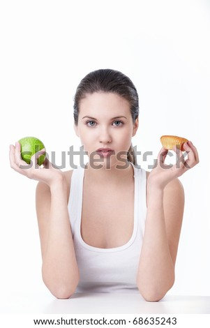 Young beautiful girl holding a green apple and cake on a white background - stock photo