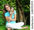 Young beautiful girl hugging her little dog near a copyspace  - stock photo