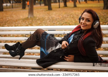 Young beautiful girl in a black coat blue dress for a walk in the autumn park