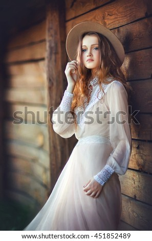 Young beautiful girl in a cowboy hat, vintage dress posing in western village. Colorful photo of  pretty long hair model outdoor.Country style.Art work.Wood background. - stock photo