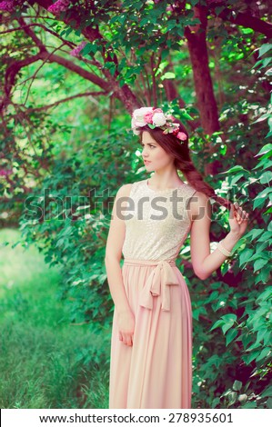 Young beautiful girl in a long dress and a wreath of flowers in the garden of lilac bush
