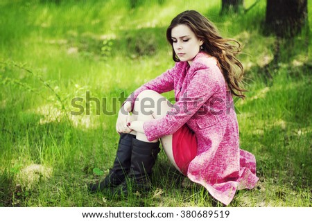 Young beautiful girl in a pink coat and pink short dress boots resting on a spring green meadow on a background of green grass. Beautiful Young Woman Outdoors. Enjoy Nature.