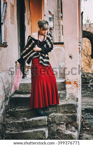 young beautiful girl in a red skirt and red corals posing against the backdrop of a collapsed house. photo plot. social issues