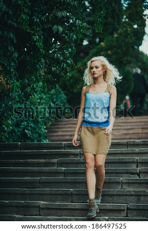 Young beautiful girl in a skirt posing near white wall. - stock photo