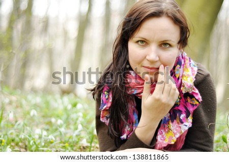 Young beautiful girl in a spring forest full of snowdrops