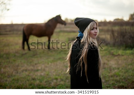 young beautiful girl in a stable, outdoors - stock photo