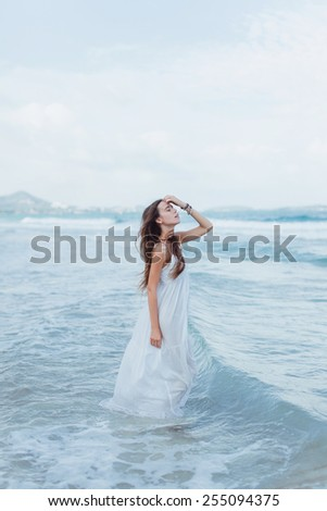 young beautiful girl in a white dress with closed eyes is on the sea with waves