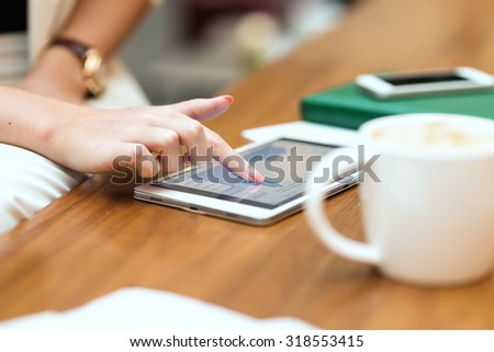 Young, beautiful girl in a white suit, sitting in a cafe and working with the tablet, graphics. - stock photo