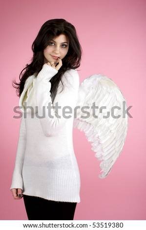 Young beautiful girl in angel suit over pink background. - stock photo