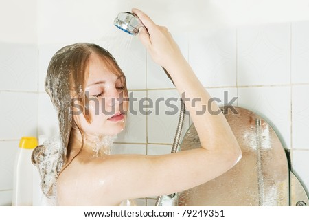 young beautiful girl in bath with shower - stock photo