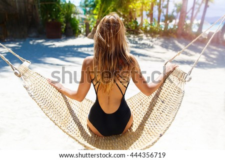 Young beautiful girl in black bathing suit with long blonde hair relaxing in hammock on the tropical beach - stock photo