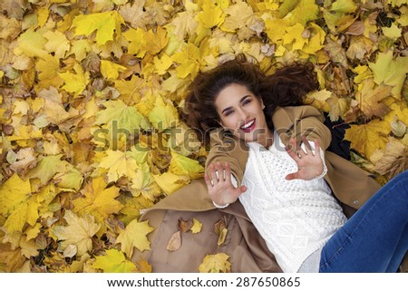 Young beautiful girl in blue jeans lying on yellow leaves, view from above, in the autumn park - stock photo