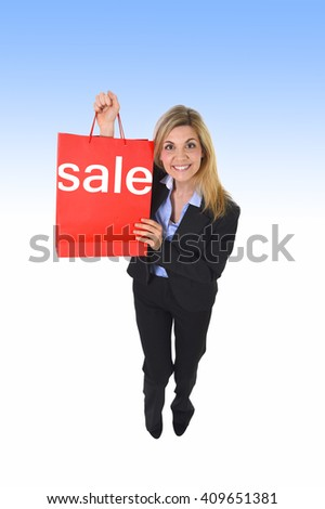 young beautiful girl in business suit in excited face expression holding red shopping bag isolated on white and blue background looking happy and excited in shopaholic and sale concept