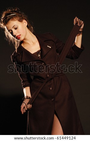 young beautiful girl in coat on black background