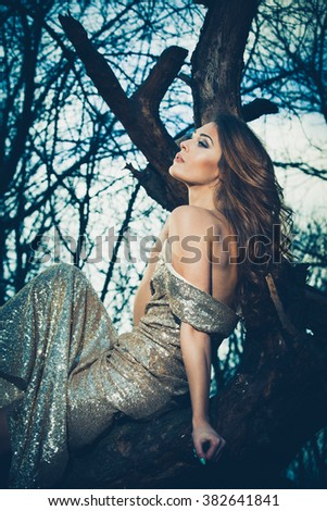 young beautiful girl in glittering long dress sit on tree in forest side view, closeup - stock photo