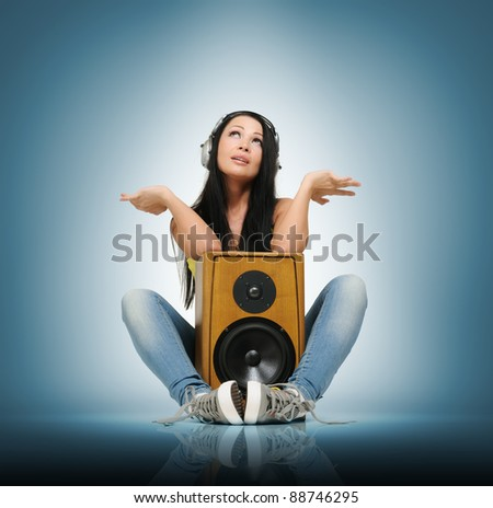 Young beautiful girl in headphones with wooden speaker, music deep concept - stock photo