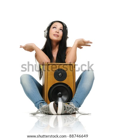 Young beautiful girl in headphones with wooden speaker on white background - stock photo