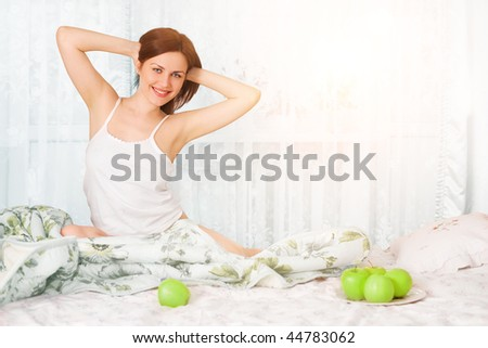 young beautiful girl in her bed with apples in morning