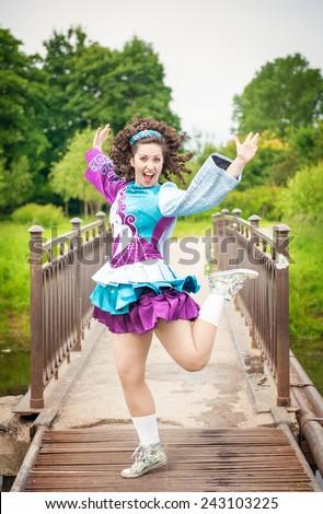 Young beautiful girl in irish dance dress and wig having fun outdoor - stock photo