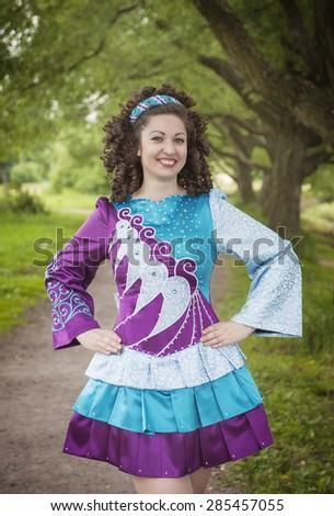 Young beautiful girl in irish dance dress and wig posing outdoor - stock photo