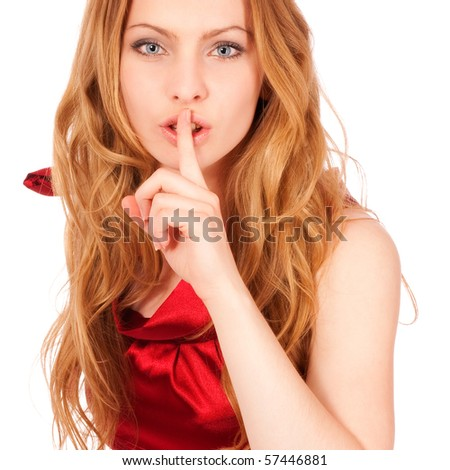 Young beautiful girl in red dress calls for silence, it is isolated on white background. - stock photo