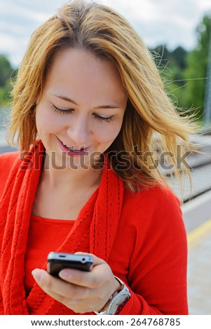 Young beautiful girl in red using mobile phone. Shallow depth of field. Focus on the left eye - stock photo