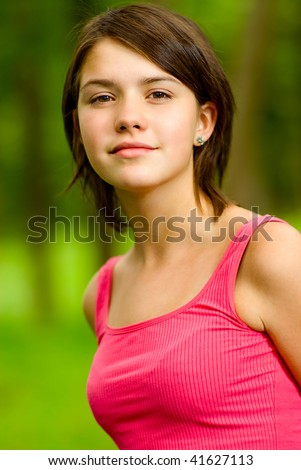Young beautiful girl in red vest costs on glade of green summer wood. - stock photo