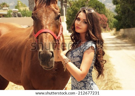 Young beautiful girl in sexy blue dress posing with brown horse at nature in summer. Fashion style portrait of pretty stylish woman