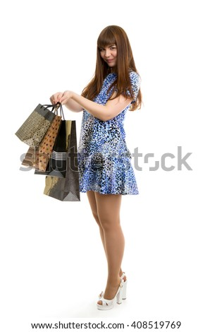 Young beautiful girl in summer dress with shopping bags in her hands isolated on white background