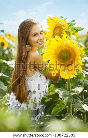 young beautiful girl in the field of sunflowers - stock photo